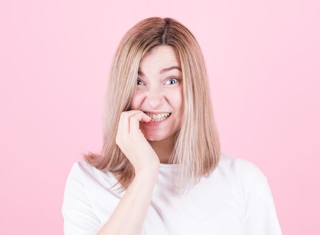 Close-up portret van een bezorgde tiener meisje in wit t-shirt haar nagels bijten geïsoleerd