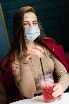 Close-up portret van een blanke vrouw die een medisch masker draagt en in de straat staat tegen de achtergrond van een café