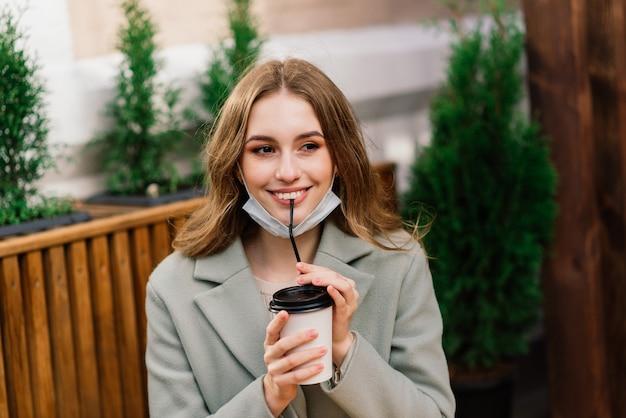 Close-up portret van een blanke vrouw die een medisch masker draagt en in de straat tegen een café staat