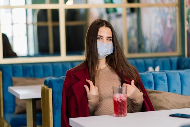 Close-up portret van een blanke vrouw die een medisch masker draagt en op straat en in het café staat