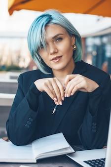 Close-up portret van een blanke vrouw met blauw haar die naar voren kijkt terwijl ze in een cafetaria zit en een laptop en enkele documenten aan het werk is