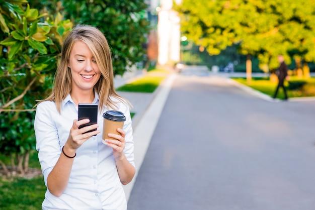 Close-up portret van een blije zakenvrouw met behulp van haar smartphone en het dragen van werkmappen, staande tegen een zonnige blauwe hemel.