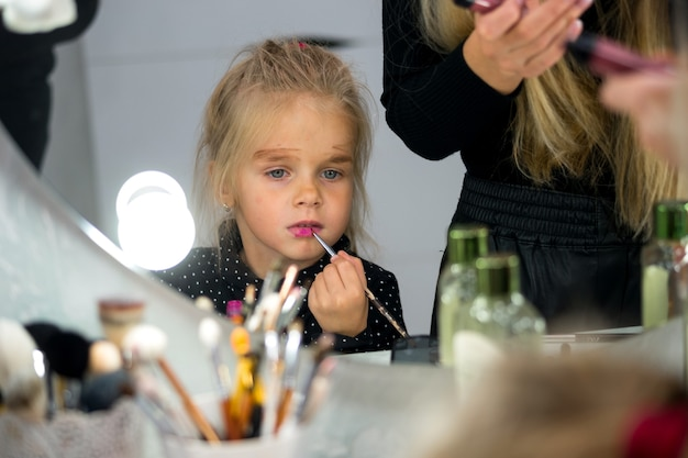 Close-up portret van een blond meisje in de weerspiegeling van de spiegel. dochter imiteert moeder en doet zelf make-up
