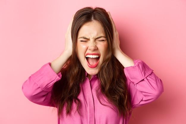 Close-up portret van een boze en beu vrouw die haar geduld verliest, schreeuwend in ontkenning, oren bedekt, geluid blokkeert, niet meer kan horen, staande over roze muur.