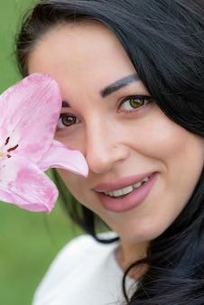Close-up portret van een brunette vrouw met een bloem.