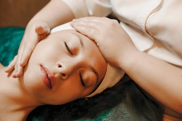 Close-up portret van een charmant vrouwelijk gezicht leunend op een spa-bed met gesloten ogen met een gezichtsmassage.