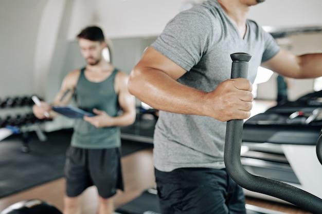 Close-up portret van een fitte man die opwarmt in een elliptische machine voordat hij gaat trainen in de sportschool