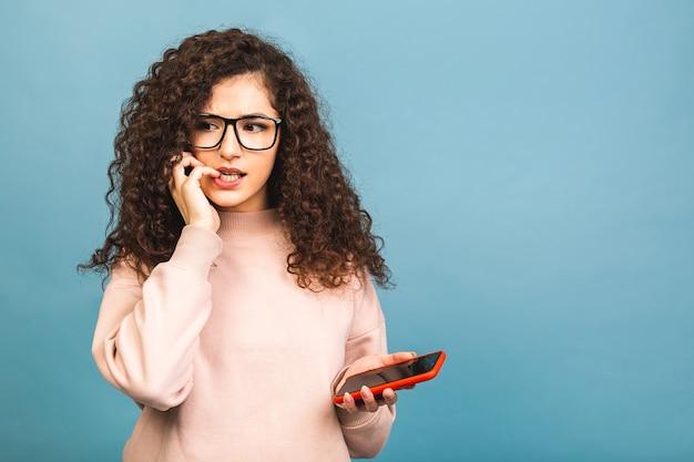 Close-up portret van een gekrulde gelukkig geschokt verbaasd vrouw in casual praten aan de telefoon geïsoleerd op blauwe achtergrond. met behulp van mobiele telefoon