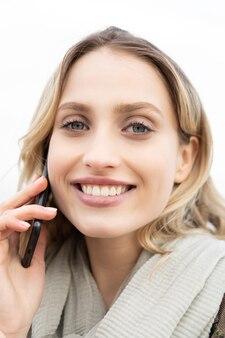 Close-up portret van een gelukkig blond meisje glimlachend en pratend op de mobiele telefoon met een verbluffende blik van haar blauwe ogen