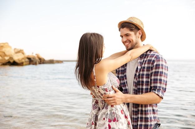 Close-up portret van een gelukkig jong hipsterpaar dat verliefd is op het strand en knuffelt