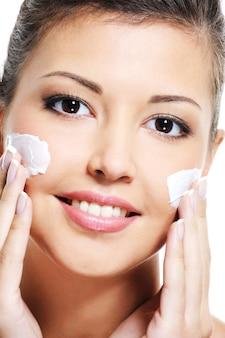 Close-up portret van een gelukkig jong vrouwelijk gezicht met een cosmetische crème op de wang