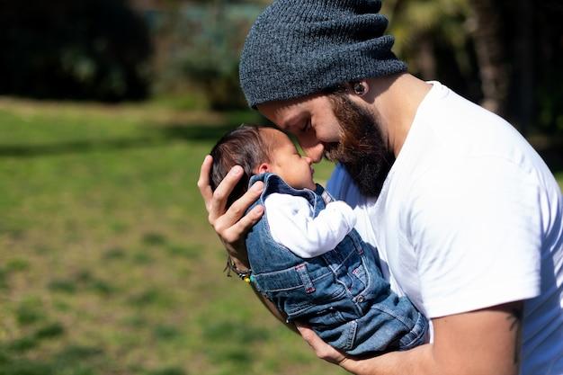 Close-up portret van een gelukkige jonge vader die zijn lief schattig pasgeboren kind knuffelt.