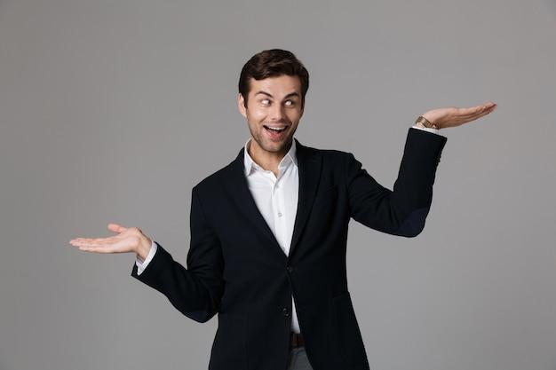 Close-up portret van een gelukkige jonge zakenman gekleed in pak geïsoleerd over grijze muur, met kopie ruimte op zijn handpalmen
