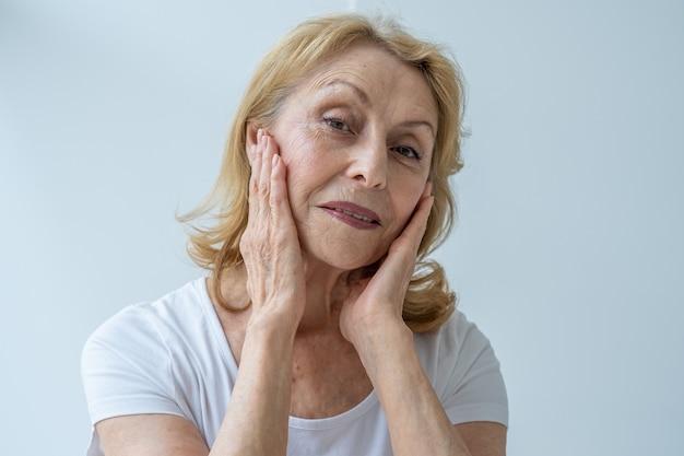 Close-up portret van een gelukkige oudere vrouw die in de spiegel kijkt en haar huid aanraakt