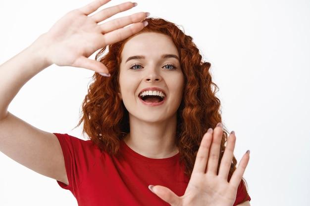 Close-up portret van een gelukkige roodharige vrouw die een handgebaar maakt, doorkijkt naar een foto of iets in beeld brengt, staande in een t-shirt tegen een witte muur
