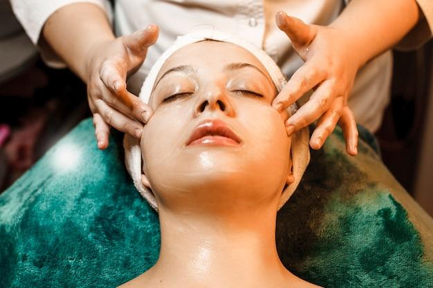 Close-up portret van een geweldige blanke vrouw met een gezichtsmassage door een vrouwelijke handen in een wellness-kuuroord terwijl ze leunend op een bed met gesloten ogen.