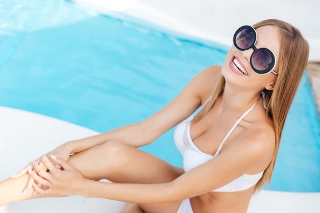 Close-up portret van een glimlachend blond meisje dat bij het zwembad zit