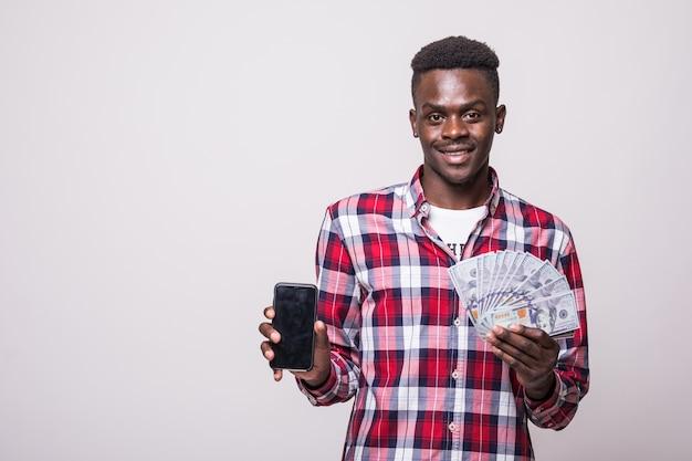 Close-up portret van een glimlachende afrikaanse man met een lege scherm mobiele telefoon terwijl hij een hoop geld bankbiljetten geïsoleerd houdt