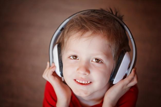 Close-up portret van een glimlachende jongen die aan muziek op hoofdtelefoons luistert.