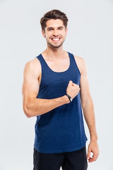 Close-up portret van een glimlachende man die zijn biceps toont geïsoleerd op een grijze achtergrond