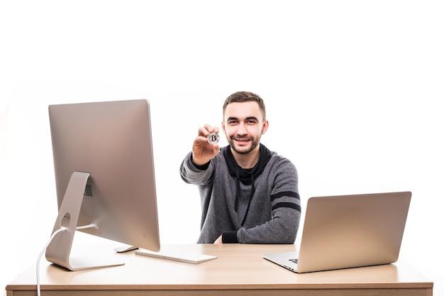 Close-up portret van een glimlachende ondernemer die bitcoin houdt zittend aan een bureau met laptop en computer geïsoleerd over wit