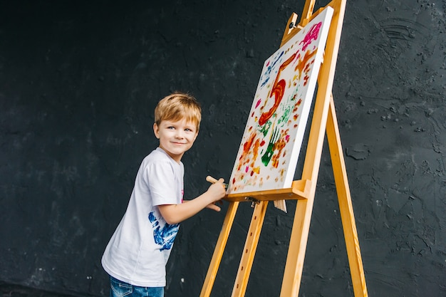 Close-up portret van een glimlachende, witte drie jaar oude jongen met een penseel in zijn hand. het concept van voorschoolse educatie, tekenen, talent, een gelukkig gezin of ouderschap