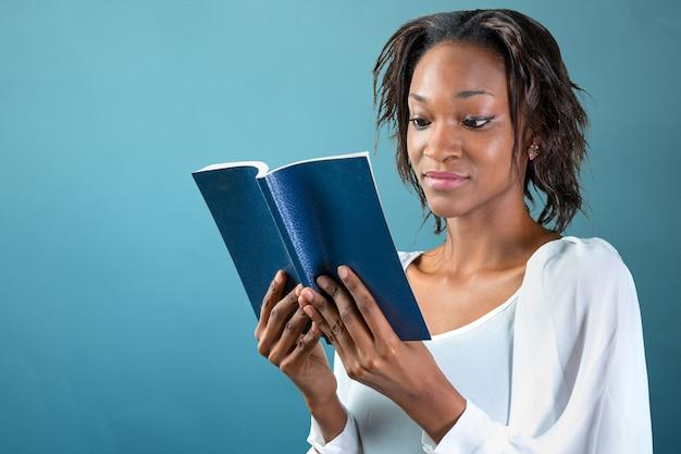 Close-up portret van een jonge afrikaanse vrouw met een boek