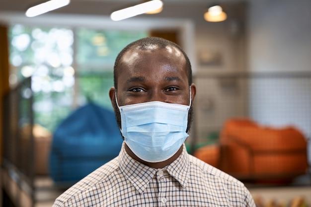 Close-up portret van een jonge afro-amerikaanse man mannelijke kantoormedewerker in beschermend gezichtsmasker op zoek naar Premium Foto