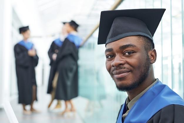 Close-up portret van een jonge afro-amerikaanse man met een afstudeerpet die vrolijk naar de camera glimlacht, kopieer ruimte