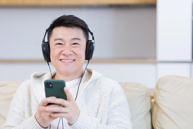Close-up portret van een jonge aziatische man die online naar muziek luistert in een koptelefoon met behulp van een mobiele telefoon