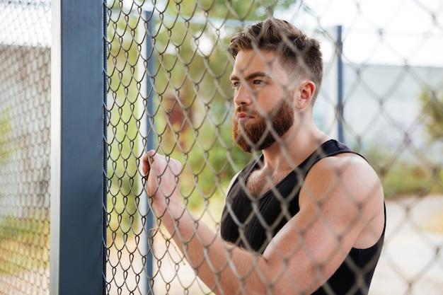 Close-up portret van een jonge, bebaarde man die buiten door een metalen stadshek kijkt
