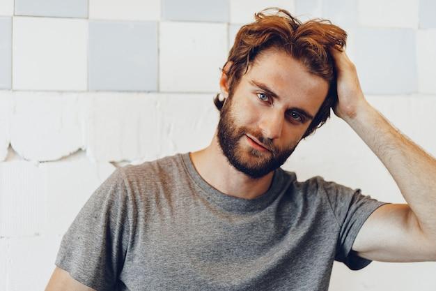 Close-up portret van een jonge, bebaarde man die tegen grunge verweerde muur
