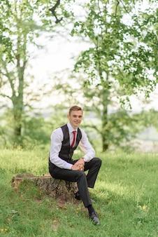 Close-up portret van een jonge bruidegom. een man zit op een boomstronk.