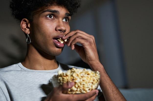 Close-up portret van een jonge kerel die popcorn eet terwijl hij thuis naar een film kijkt