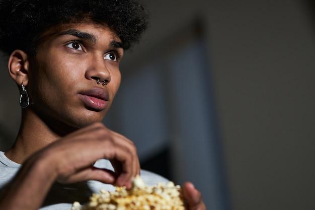 Close-up portret van een jonge kerel die wat popcorn uit een kom neemt terwijl hij thuis naar een film kijkt