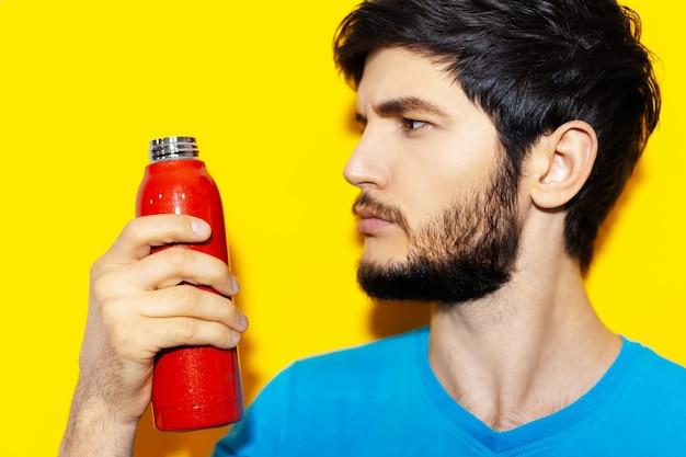 Close-up portret van een jonge kerel in blauw shirt met rode herbruikbare stalen thermo waterfles