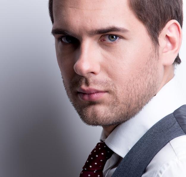 Close-up portret van een jonge knappe man in pak poseren