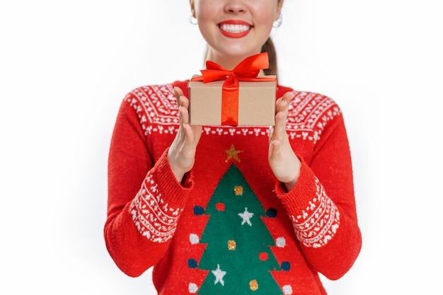 Close-up portret van een jonge lachende vrouw in een nieuwjaarssweater, die een geschenk in haar handen houdt. witte achtergrond. het concept van kerstinkopen.
