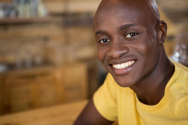 Close-up portret van een jonge man die lacht in koffiehuis