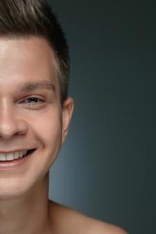 Close-up portret van een jonge man geïsoleerd op een grijze achtergrond. kaukasisch mannelijk model direct kijken en poseren, glimlachend.