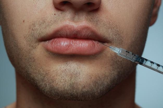Close-up portret van een jonge man geïsoleerd op een grijze achtergrond. operatieprocedure vullen.