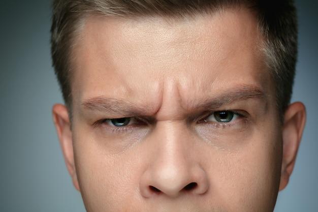 Close-up portret van een jonge man geïsoleerd op een grijze muur. kaukasisch mannelijk model camera kijken en poseren, ziet er serieus uit. concept van de gezondheid en schoonheid van mannen, zelfzorg, lichaams- en huidverzorging.