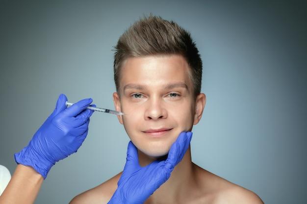 Close-up portret van een jonge man geïsoleerd op een grijze muur. vullen van chirurgische procedure, lippen en jukbeenderen. concept van de gezondheid en schoonheid van mannen, cosmetologie, lichaams- en huidverzorging. anti-veroudering.
