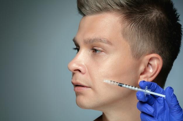 Close-up portret van een jonge man geïsoleerd op een grijze muur. vullen van operatieprocedure, lippen en jukbeenderen. concept van de gezondheid en schoonheid van mannen, cosmetologie, lichaams- en huidverzorging. anti-veroudering.