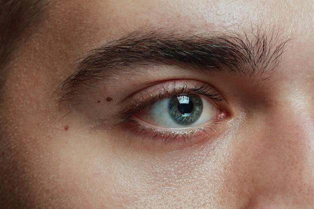 Close-up portret van een jonge man geïsoleerd op grijze studio achtergrond. kaukasisch mannelijk model gezicht en blauw oog. concept van de gezondheid en schoonheid van mannen, zelfzorg, lichaams- en huidverzorging, geneeskunde of fycologie.