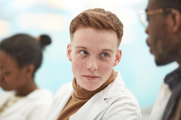 Close-up portret van een jonge man met een laboratoriumjas terwijl hij in de rij zit in het publiek en luistert naar een lezing over geneeskunde op de universiteit, kopieer ruimte