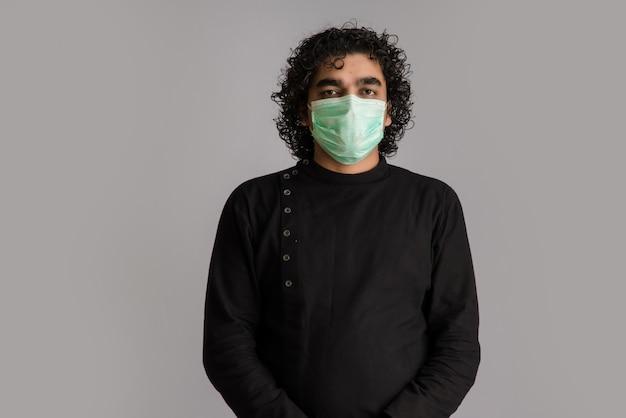 Close-up portret van een jonge man met een medisch of chirurgisch masker