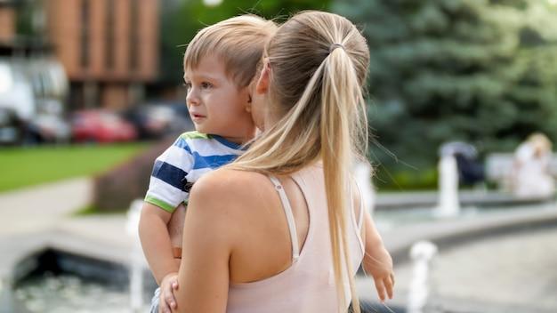 Close-up portret van een jonge moeder die haar huilende kleine kindjongen in het park knuffelt en streelt