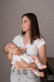 Close-up portret van een jonge moeder. een vrouw heeft een pasgeboren baby in haar armen.
