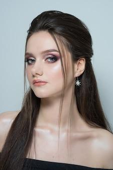 Close-up portret van een jonge mooie vrouw. close-up portret van een mooie jonge brunette vrouw met lang haar en avond make-up